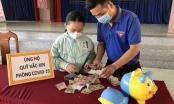 Một học sinh đập heo đất ủng hộ Quỹ vaccine phòng dịch Covid-19